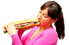 Young woman eating a freshly made sub sandwich Royalty Free Stock Image