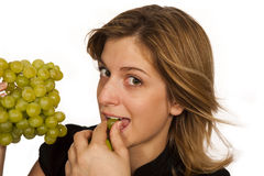 Young woman eating fruit. Young woman eating green wine grape over white background Royalty Free Stock Photography