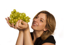 Young woman eating fruit. Young woman eating green wine grape over white background Stock Image