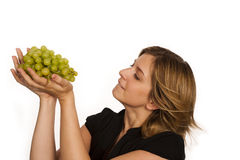 Young woman eating fruit. Young woman eating green wine grape over white background Stock Images