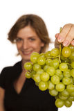 Young woman eating fruit. Young woman eating green wine grape over white background Stock Photo
