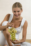 Young woman eating fruit. Attractive young woman with fruit, healthy lifestyle Royalty Free Stock Photography