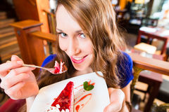 Young woman eating fruit cake. At cafe or bakery Stock Image