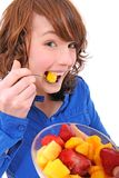 Young woman eating fruit salad. Happy young woman eating fruit salad stock photography