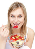 Young woman eating a fruit salad Stock Images