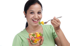 Young woman eating fruit salad Royalty Free Stock Photos