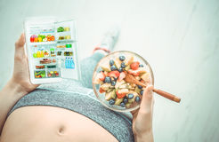 Young woman is eating a fruit salad and using a fitness app on her smartphone after a workout. stock photo