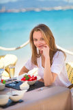 Young woman eating fruits in a beach restaurant Stock Image