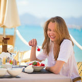 Young woman eating fruits in a beach restaurant Royalty Free Stock Photography