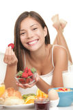 Young woman eating fruits at breakfast Royalty Free Stock Images