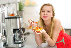 Young woman eating fruits salad in kitchen Stock Images
