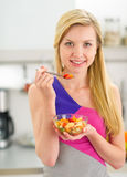 Young woman eating fruits salad in kitchen Royalty Free Stock Photo