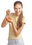 Young woman eating grapefruit Stock Images