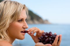 Young woman eating grapes stock images