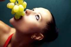 Young woman eating grapes. Stock Images