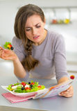 Young woman eating greek salad in kitchen and read Stock Images