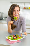 Young woman eating greek salad and watching tv Stock Photos
