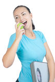 Young woman eating green apple and  holding weght Stock Images