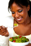 Young woman eating green salad on a bowl Royalty Free Stock Photos