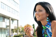 Young woman eating hamburger outdoors Royalty Free Stock Photos