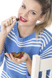 Young Woman Eating a Handful of Sweets Stock Photo