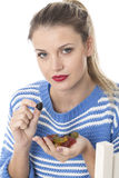 Young Woman Eating a Handful of Sweets Stock Photography