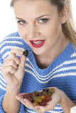 Young Woman Eating a Handful of Sweets Royalty Free Stock Photos