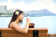 Young woman eating Hawaiian bqq beef on bench in Hawaii Royalty Free Stock Images