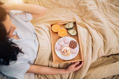 Young woman eating healthy breakfast in bed. Cropped photo of woman sitting in bed with cream color blanket and having breakfast. Top view. Healthy and tasty stock photo