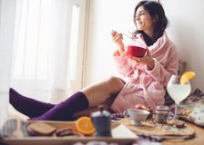 Young woman eating healthy breakfast. Young woman eating healthy breakfast, early in the morning stock images