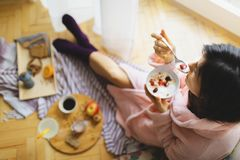 Young woman eating healthy breakfast. Young woman eating healthy breakfast, early in the morning royalty free stock photos