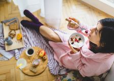 Young woman eating healthy breakfast. Young woman eating healthy breakfast, early in the morning stock image