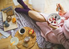 Young woman eating healthy breakfast. Young woman eating healthy breakfast, early in the morning royalty free stock image