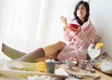 Young woman eating healthy breakfast. Young woman eating healthy breakfast, early in the morning royalty free stock photo