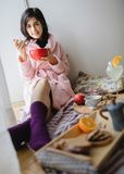 Young woman eating healthy breakfast. Young woman eating healthy breakfast, early in the morning stock photography