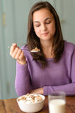 Young woman eating healthy cereal breakfast Royalty Free Stock Photography