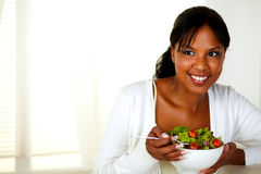 Young woman eating healthy salad. Portrait of a young woman eating healthy salad at home indoor. With copyspace Stock Photos
