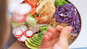 Young woman is eating a healthy salad bowl. Young woman is eating a healthy salad bowl with quinoa, chicken, avocado and vegetables