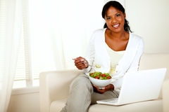 Young woman eating healthy salad looking at you. Portrait of a young woman eating healthy salad and looking at you while is sitting on couch in front of her Royalty Free Stock Images
