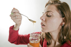 Young woman eating honey Royalty Free Stock Images
