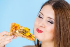 Woman eating hot pizza slice stock photography