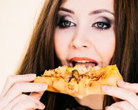 Woman eating hot pizza slice royalty free stock photography