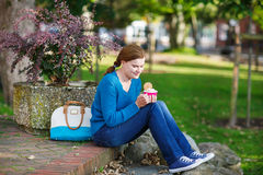 Young woman eating ice cream in summer park. Royalty Free Stock Image