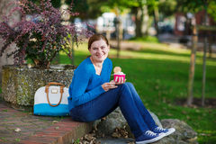 Young woman eating ice cream in summer park. Royalty Free Stock Photos