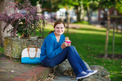 Young woman eating ice cream in summer park. Stock Photos