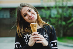 Young woman eating ice-cream sunny day outdoors Stock Images