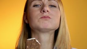 Young woman eating ice cream on a yellow background stock video footage