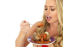 Young Woman Eating a Jacket Potato with Baked Beans Stock Photography
