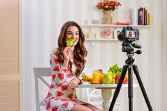 Young woman eating lettuce. Young woman eating a leaf of lettuce. Concept of popularization of plant food diet through video blog stock photography