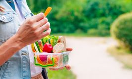 Young woman eating from lunch box outdoor. Healthy food concept: Young woman eating from lunch box filled with sandwich, crispbreads, fruits and vegetables royalty free stock image